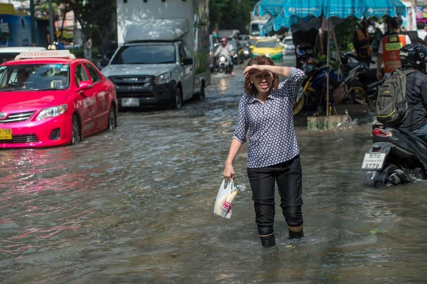 A woman crosses a flooded intersection in Bangkok, on Oct 14, 2017. Thailand is currently in the middle of its rainy season, which often generates flash storms.