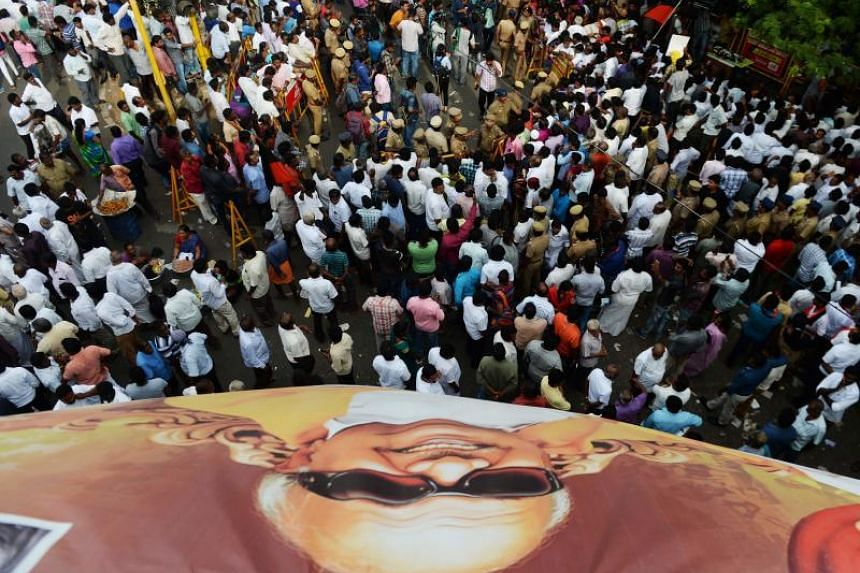 Dravida Munnetra Kazhagam party supporters gather under a large banner with the portrait of party president Muthuvel Karunanidhi in front of hospital where he died, in Chennai, on Aug 7, 2018.