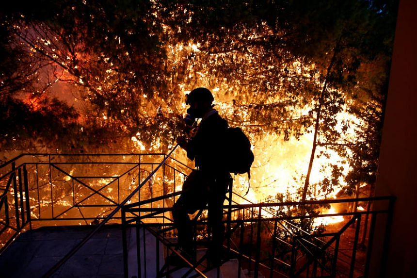 A volunteer sprays water as a wildfire burns in the town of Rafina, near Athens, Greece, on July 23, 2018.