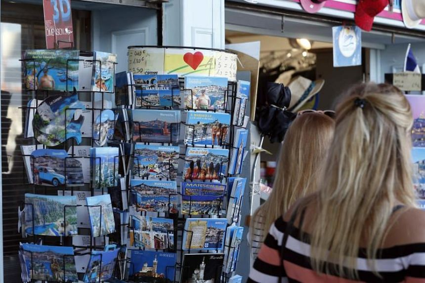 Women walk past a rack that displays postcards, some with pictures of bikini-clad women, on a stand at a souvenir shop in Marseille, France, on Aug 6, 2018.