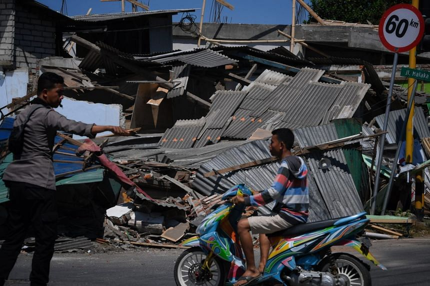 Collapsed buildings are seen at an intersection near the jetty off North Lombok ferrying passengers to and fro the Gili Islands on Aug 7, 2018.