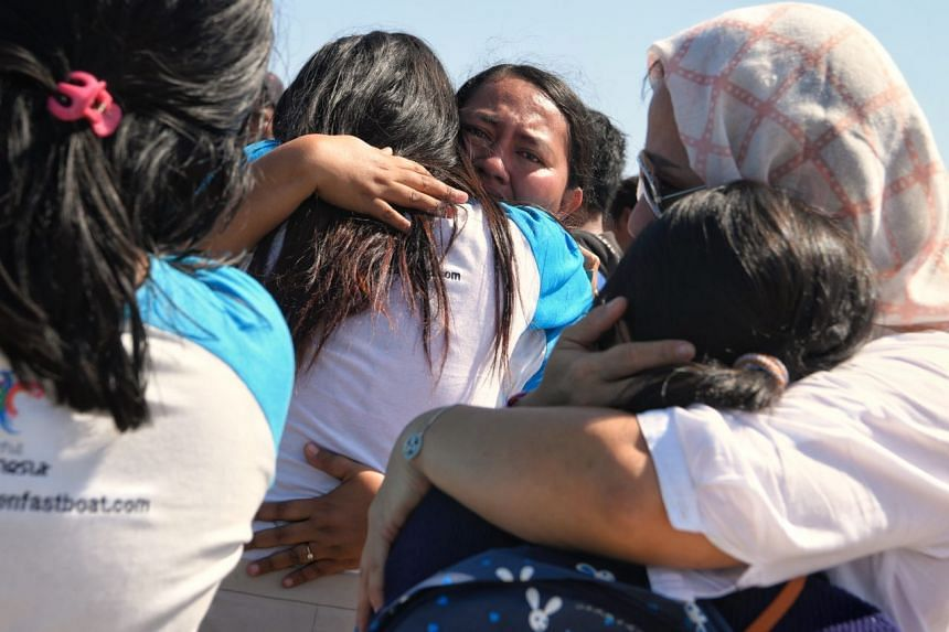 Staff from boat services Golden Queen Fastboat, who were picked up from various islands where they worked, hug their family members after arriving at the Bangsal Jetty off North Lombok on Aug 7, 2018.