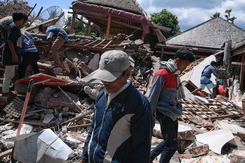 Villagers search for Dea Mukti, 21, who is believed to be trapped under the rubble in the village of Karang Montong Laut on Indonesia's Lombok island, on Aug 7, 2018.