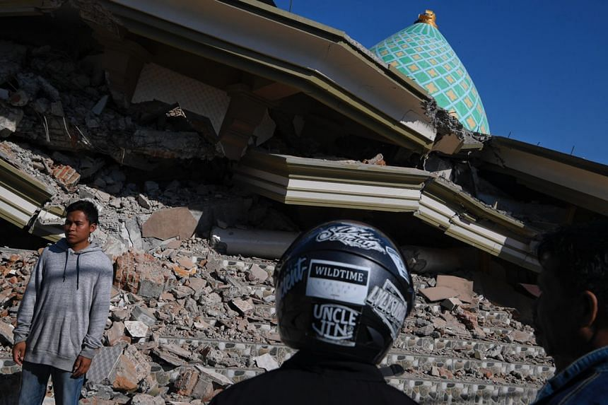 Lalu Fauzan (left) standing beside the collapsed Jami'ul Jama'ah mosque, where his mother is trapped under the rubble, in North Lombok on Aug 7, 2018.