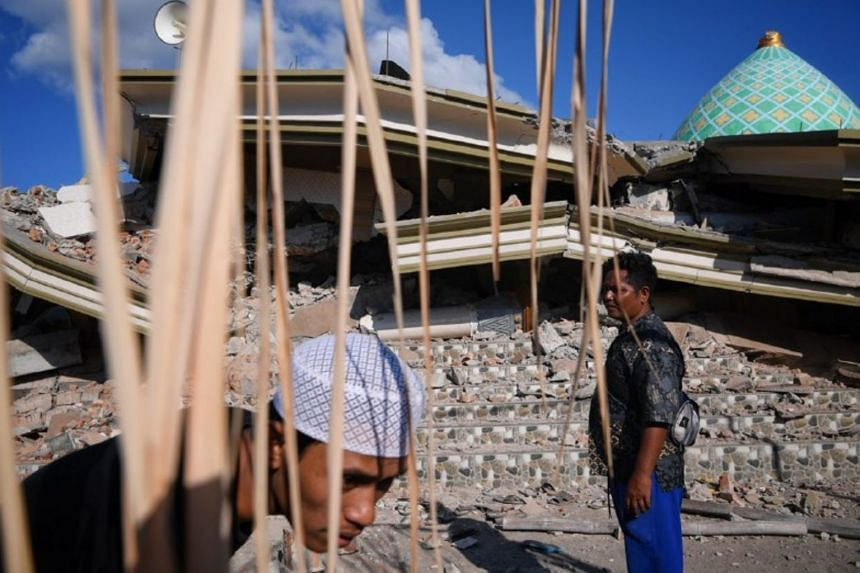 Villagers of Karang Pangsor including Yuspiadi (right), in his 30s, at the collapsed Jami'ul Jama'ah mosque, which has at least five people still stuck under the rubble.