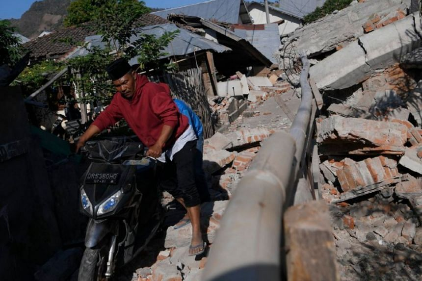 Villagers of Karang Pangsor helping to remove motorcycles near the collapsed Jami'ul Jama'ah mosque, which has at least five people still stuck under the rubble.