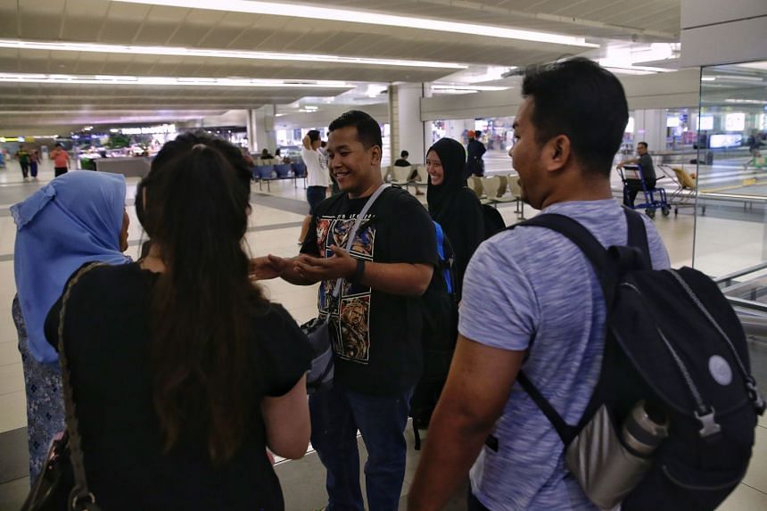 Family members welcoming Mr Muhammad Ashraf Arsat (centre), 31, and his wife Nur Zafirah Sulaiman, 30, at Changi Airport, on Aug 6, 2018. The couple was on their honeymoon in Lombok when a 7-magnitude earthquake struck the resort island.