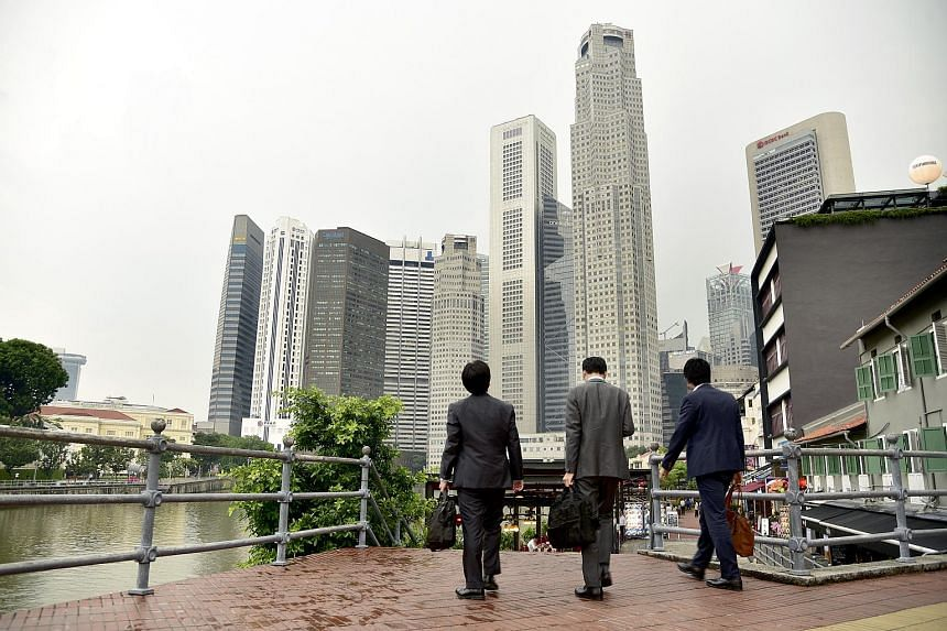 Office workers along Singapore River walking towards the central business district, on April 25, 2017.