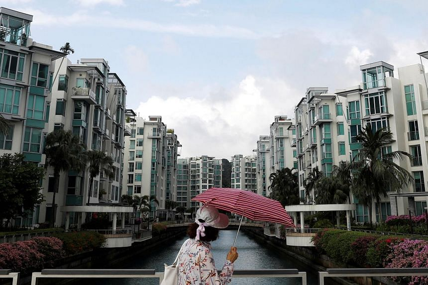 File photo showing a woman walking past a private condominium in Singapore, on Feb 13, 2017.