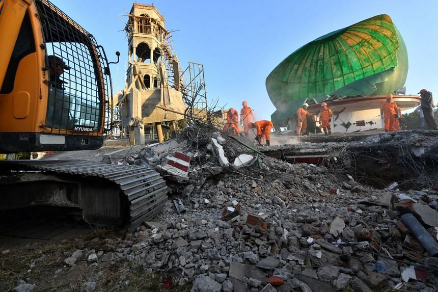 Indonesian search and rescue personnel work on a collapsed mosque in Pemenang, North Lombok, on Aug 6, 2018, the day after a 6.9 magnitude earthquake struck the area.
