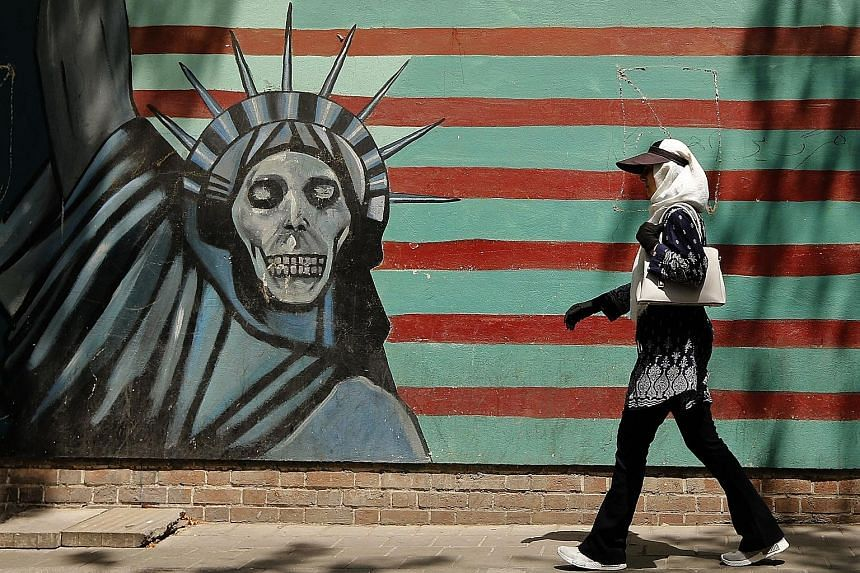 A mural on the wall of the former United States embassy in Teheran. The American sanctions target Iran's access to US dollars.