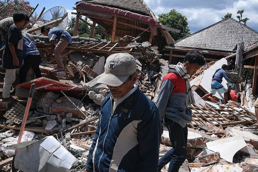 Rescuers searching for survivors yesterday. Many are struggling to reach those trapped in the rubble of collapsed buildings on Lombok. The quake has killed 105 people, including two in neighbouring Bali, and injured more than 230 others.