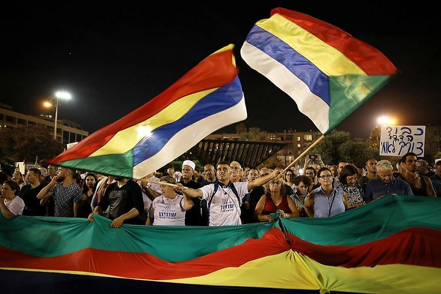 A protester waving the Druze community's flags in a rally against the Jewish nation-state law in Rabin Square in Tel Aviv last Saturday. Israel's prominent figures, including mayors and former chiefs of staff, have joined the protest.