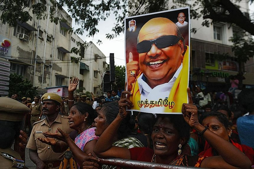 A Dravida Munnetra Kazhagam party supporter holding a portrait of party president M. Karunanidhi in front of the Chennai hospital where he died yesterday.