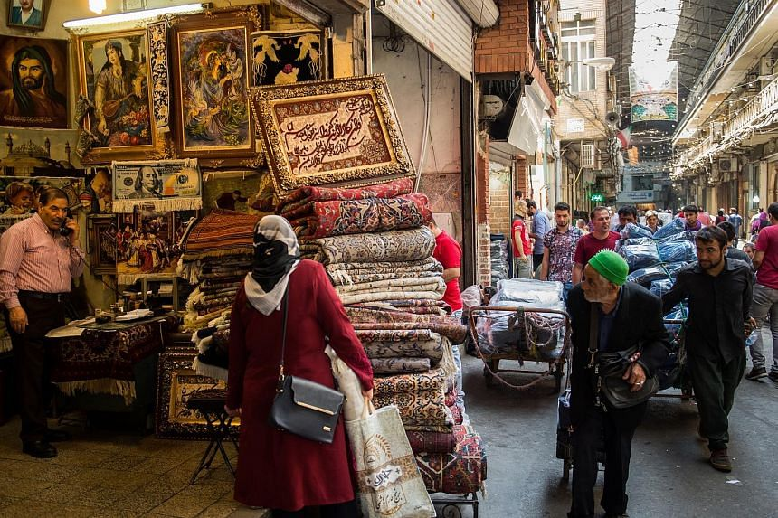"""Carpet traders wheeling their wares past a store selling Persian rugs in Teheran's Grand Bazaar. Many Iranians blame their own government for the return of US sanctions, but they also fear it could be the """"final nail in the coffin"""" for the flounderin"""