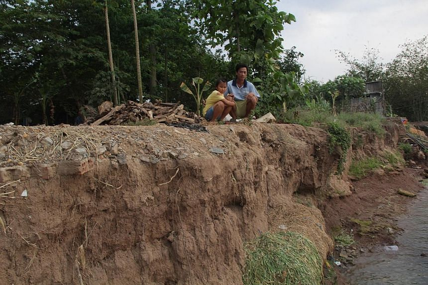 Mr Nguyen Van Huy and his daughter Nguyen Thi Em Ri, eight, at the riverbank where their home used to be before it collapsed into the river. Sand dredgers are common on the Tien River between An Giang Province and Dong Thap Province in southern Vietn
