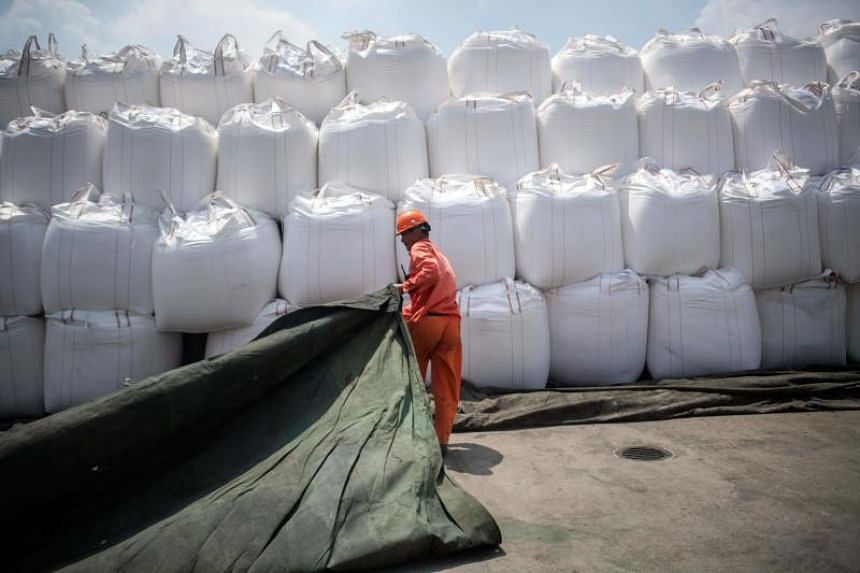 A worker covering bags of chemicals with a sheet at a port in Zhangjiagang in China's eastern Jiangsu province, on Aug 7. 2018. Chemicals are on the Chinese list of goods that will incur a 25 per cent duty.