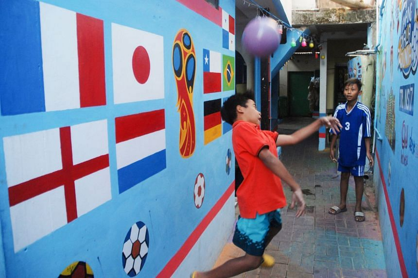 Indonesian boys playing with a plastic ball at a village decorated with the 2018 Russia World Cup football theme in Cimahi.