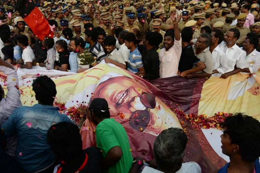 Indian supporters hold onto a large banner with a picture of Dravida Munnetra Kazhagam (DMK) party president M. Karunanidhi during the funeral procession, in Chennai, on Aug 8, 2018.