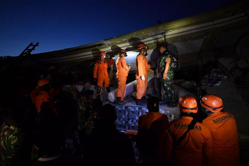 Rescuers looking for victims in the rubble of a mosque in Pemenang, northern Lombok, on Aug 7, 2018.