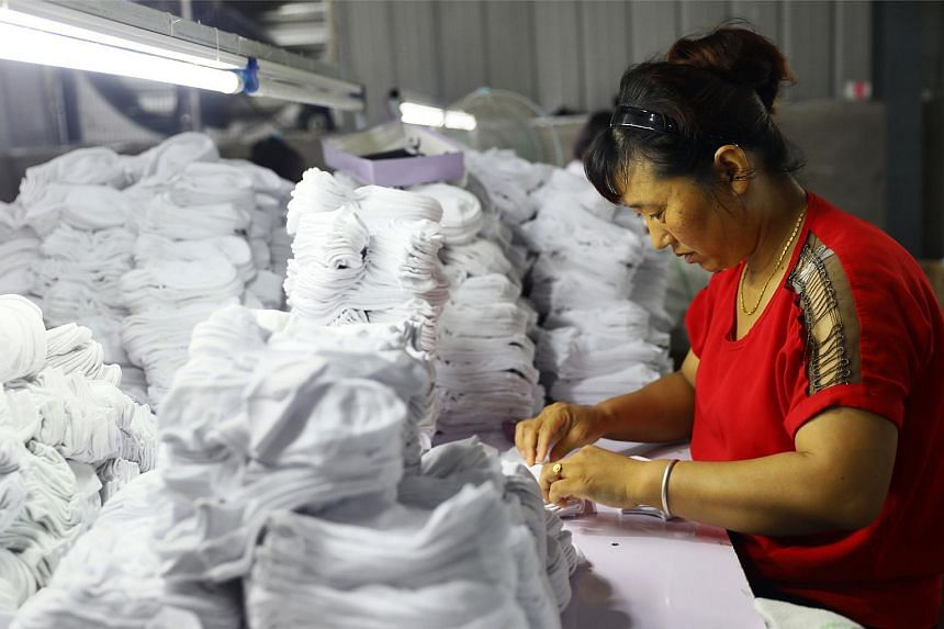 A woman works on socks that will be exported to the US at a factory in Anhui, China, on Aug 7, 2018.