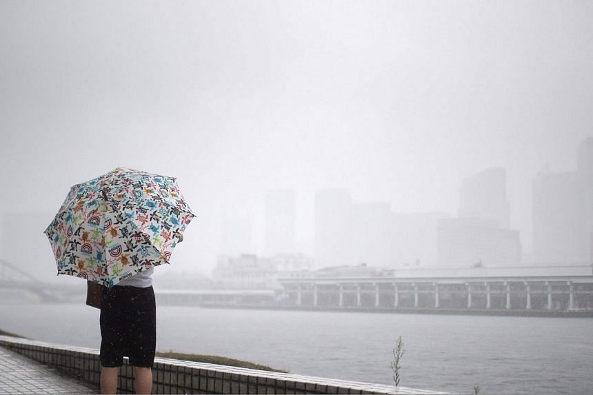 A woman protects herself from the rain with an umbrella in Tokyo on July 28, 2018.