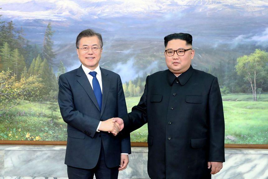 South Korean President Moon Jae-in (left) and North Korean ruler Kim Jong Un shaking hands at the truce village of Panmunjom.