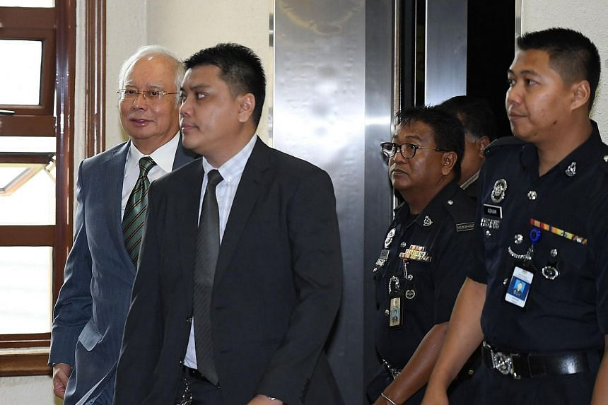 Former Malaysia prime minister Najib Razak (left) is transferred to a high court after an appearance at the Duta court complex in Kuala Lumpur, on Aug 8, 2018.