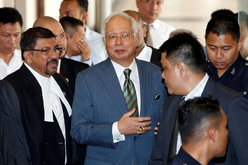 Malaysia's former prime minister Najib Razak (centre) walks out of a courtroom in Kuala Lumpur, on Aug 8, 2018.
