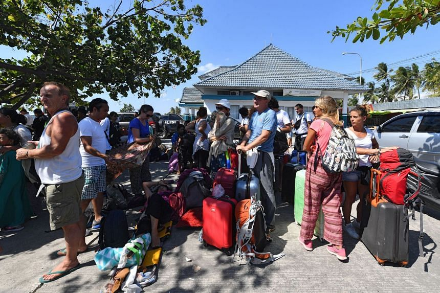 A tourist being given a helping hand yesterday at Bangsal Port in northern Lombok. Evacuated travellers (above) were arriving in Bangsal from nearby Gili Trawangan on Monday, following the magnitude-7 quake.