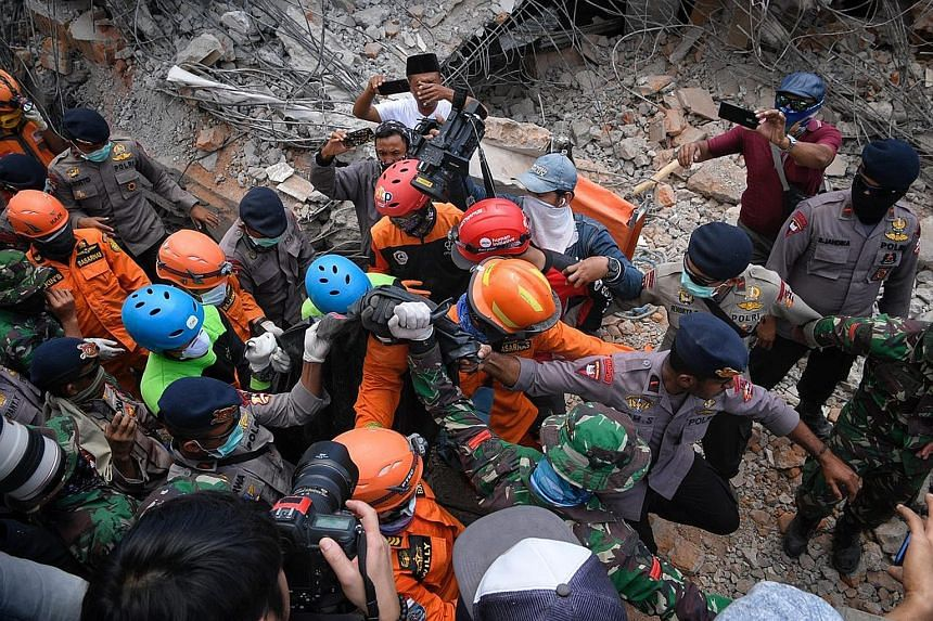 Rescuers working to remove debris at the Jami'ul Jama'ah mosque. Villagers had just performed their evening prayer on Sunday when the earthquake struck, causing the mosque to collapse. A body being removed from the rubble of the Jami'ul Jama'ah mosqu