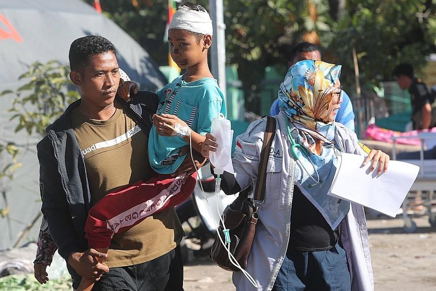 A father carrying his injured son being accompanied by a volunteer doctor at an emergency hospital in Tanjung, North Lombok, yesterday.