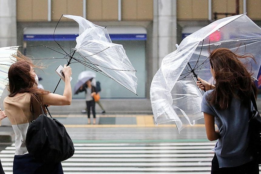 Pedestrians with umbrellas struggling against heavy rain and winds as Typhoon Shanshan approached Tokyo yesterday. The meteorological agency warned that the typhoon could dump 350mm of rain over the greater Tokyo region by noon today.