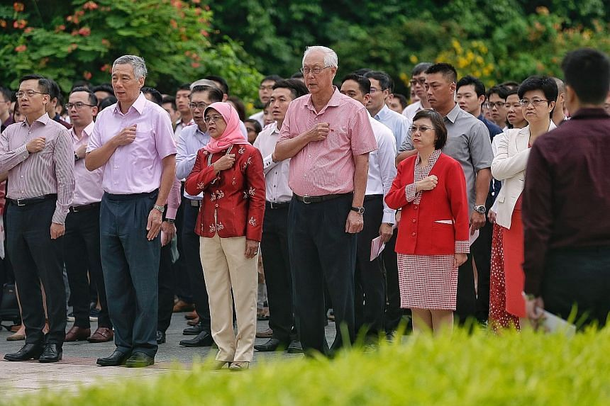 President Halimah Yacob, flanked by PM Lee Hsien Loong and ESM Goh Chok Tong, reciting the Singapore Pledge with 400 staff members of the Istana, Prime Minister's Office, Military Police Command and NParks at a National Day Observance Ceremony yester