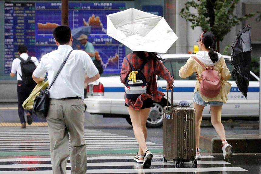 People using umbrellas struggle against a heavy rain and wind in front as Typhoon Shanshan approaches Japan's mainland in Tokyo, Japan, on Aug 8, 2018.