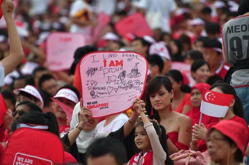 National Day Parade attendees raising plaques with handwritten messages on them.