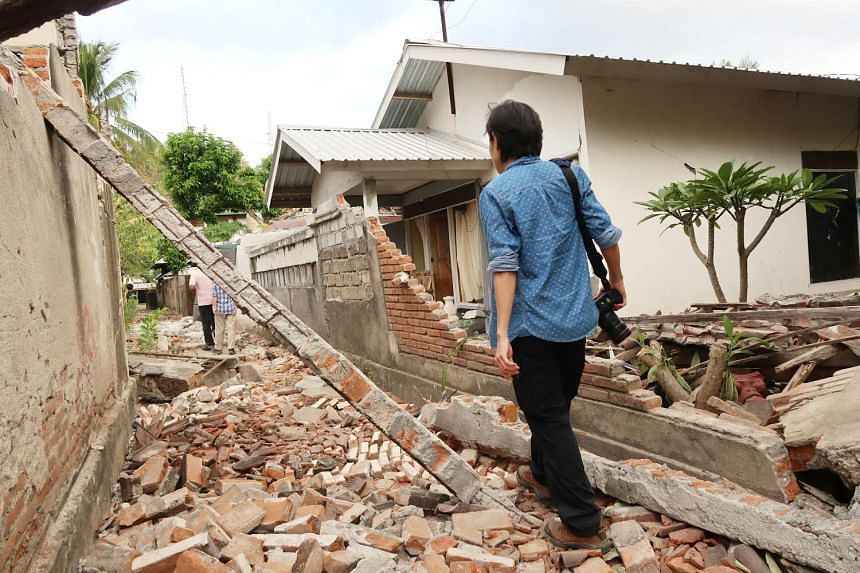 Singapore Red Cross volunteer Lee Siew Yian walks through the rubble in a village in West Lombok, where she is in for relief efforts.