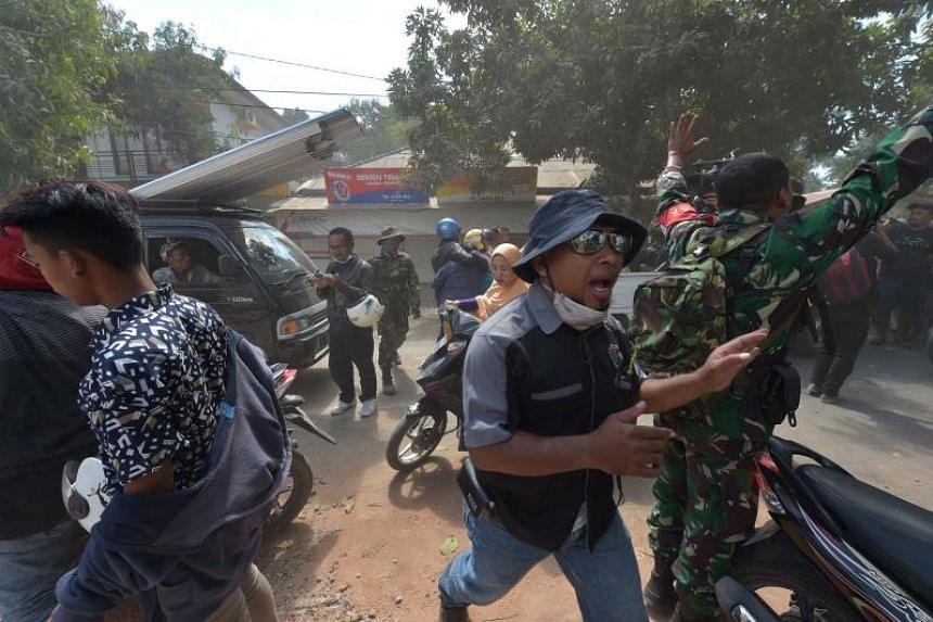 An Indonesian soldier and an official try to calm people shortly after an aftershock hits the area in Tanjung on Indonesia's Lombok island on Aug 9, 2018.