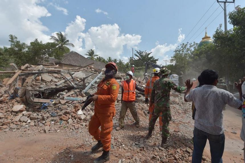 Indonesian search and rescue members react shortly after an aftershock hits the area in Tanjung on Lombok island on Aug 9, 2018.