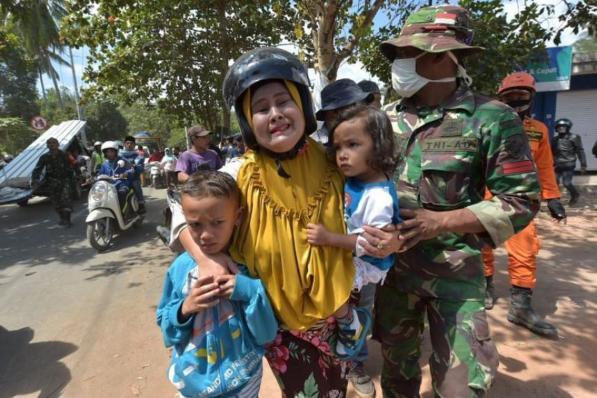 A woman cries next to her children shortly after an aftershock hits the area in Tanjung on Indonesia's Lombok island on Aug 9, 2018.