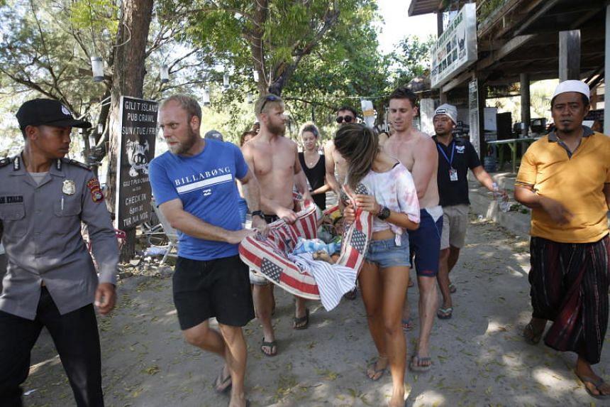 Tourists help an Indonesian woman in Gili Trawangan  after an earthquake struck nearby Lombok island on Aug 9, 2018.
