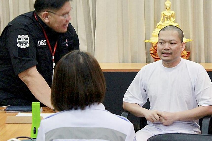 Former Thai Buddhist monk Nen Kham, also known as Wiraphon Sukphon (right), being questioned by a Department of Special Investigation (DSI) officer at the DSI headquarters in Bangkok on July 19, 2017.