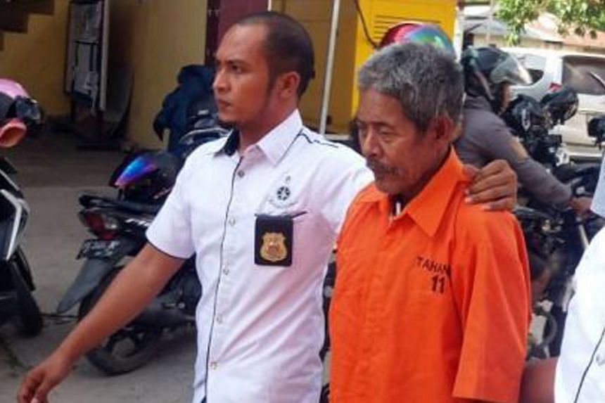 A police officer escorting the 83-year-old shaman, Jago, who faces 15 years in prison, in Tolitoli regency, Central Sulawesi, on Sunday.