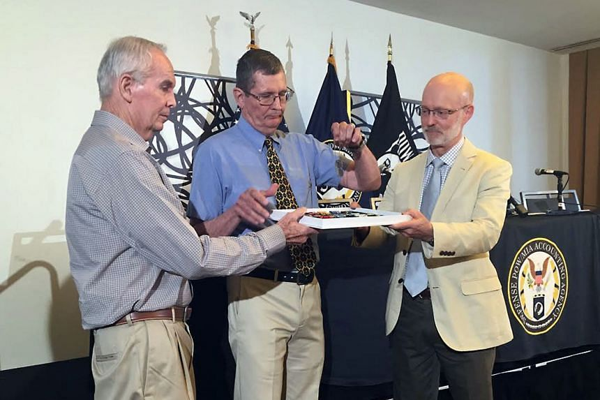 Larry McDaniel (left) and brother Charles McDaniel Jr (centre) receive their father's military identity tags.