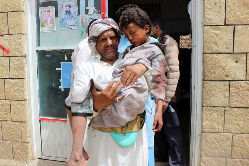 A man transports a child to a hospital after he was wounded in a reported air strike in Saada.