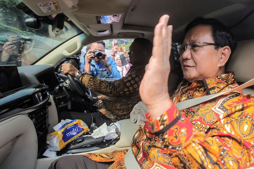Gerindra Party leader Prabowo Subianto waves to reporters as he arrives for a meeting with former Indonesian president Susilo Bambang Yudhoyono at the Yudhoyono's residence in Jakarta on Aug 9, 2018.