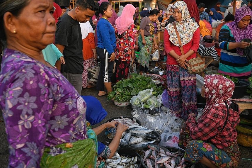 Traders selling their goods on makeshift stalls outside the market building at Gunung Sari wet market in West Lombok yesterday.