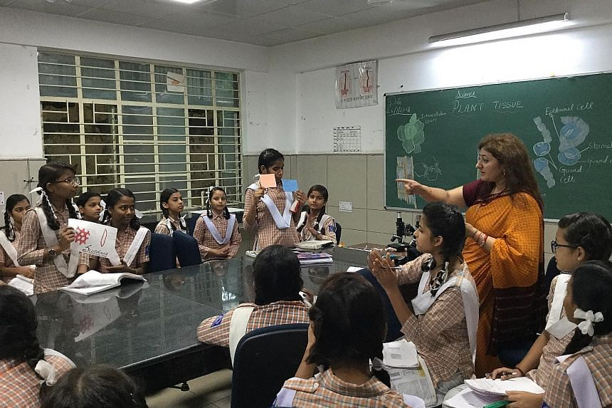 Ninth grade students from Mandawali's Sarvodaya Kanya Vidyalaya No. 2, a government-run school, engage in a group discussion with their science teacher. The use of learning techniques like group discussions is part of a radical shift under way in Del