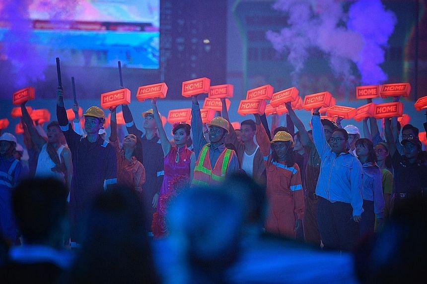 """Performers holding up lighted bricks with the word """"Home"""" inscribed on them during the first act, which represents the coming together of people from all walks of life to build Singapore."""