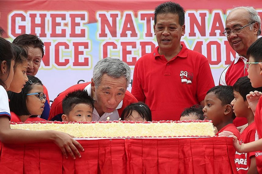 Prime Minister Lee Hsien Loong blowing out candles on a cake together with children from the PAP Community Foundation at the Teck Ghee National Day observance ceremony yesterday. On Mr Lee's left are Mr Dee Kim Hua, organising chairman of the ceremon
